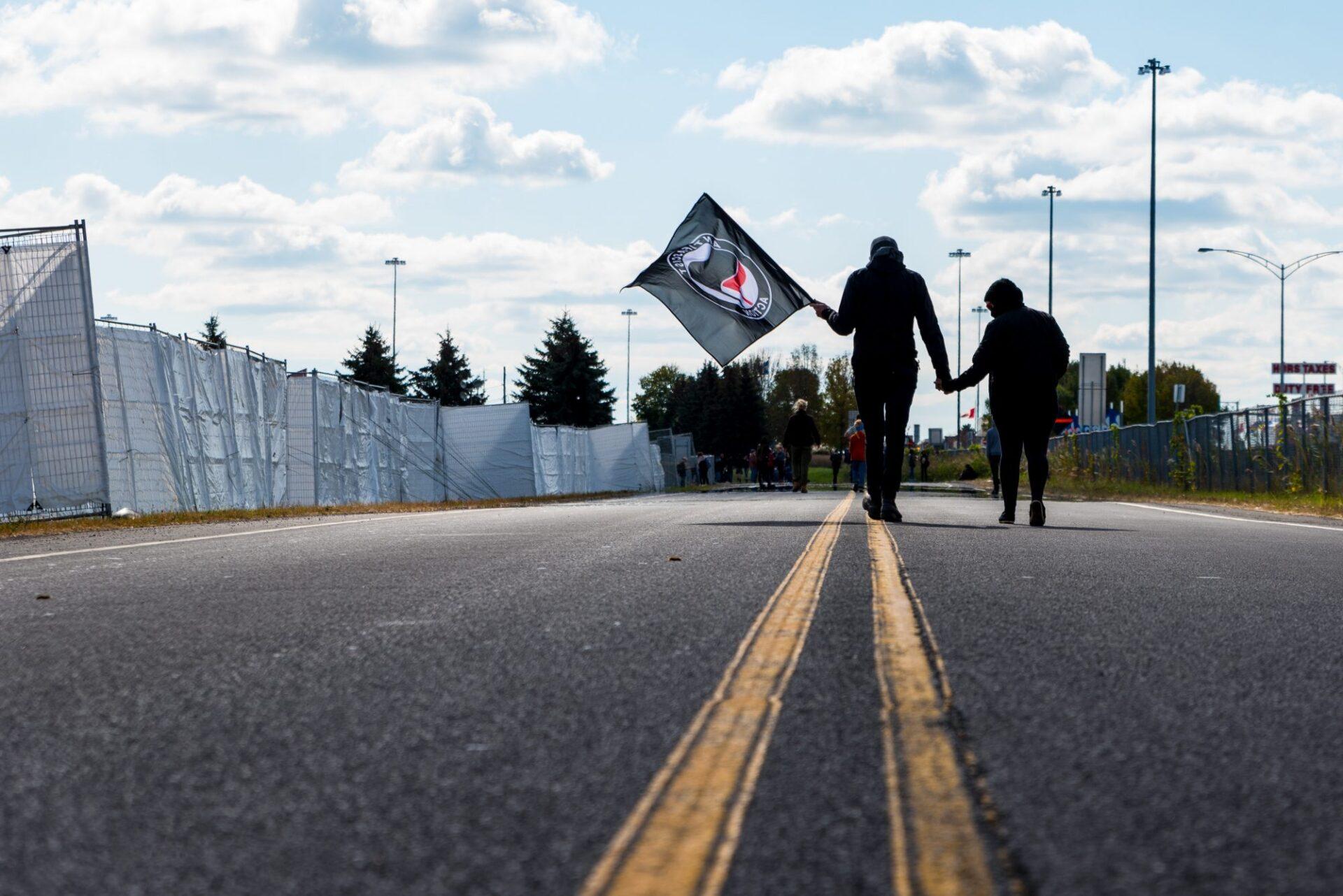 Un manifestant et une manifestante antifasciste marchent le long du camp de réfugiés près de la frontière   Photo: Martin Ouellet-Diotte Montréal Campus
