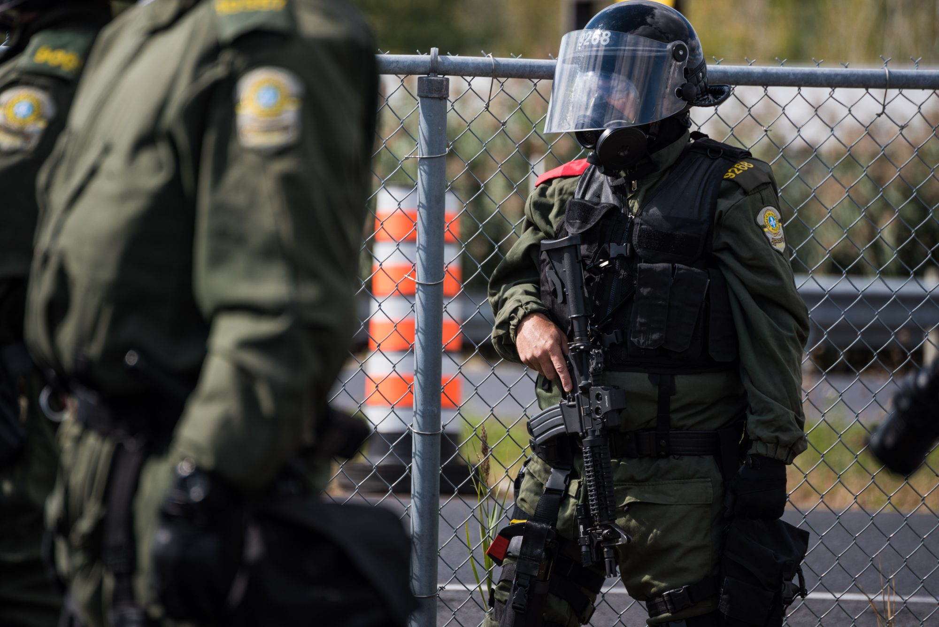 Un fusil d'assaut déployé sur un des agents de la Sûreté du Québec observant les deux manifestations   Photo: Martin Ouellet-Diotte Montréal Campus